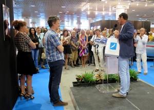 David Lisnard, maire de Cannes détaillant le contenu du pack à Michel Gondry devant un parterre de sourires.